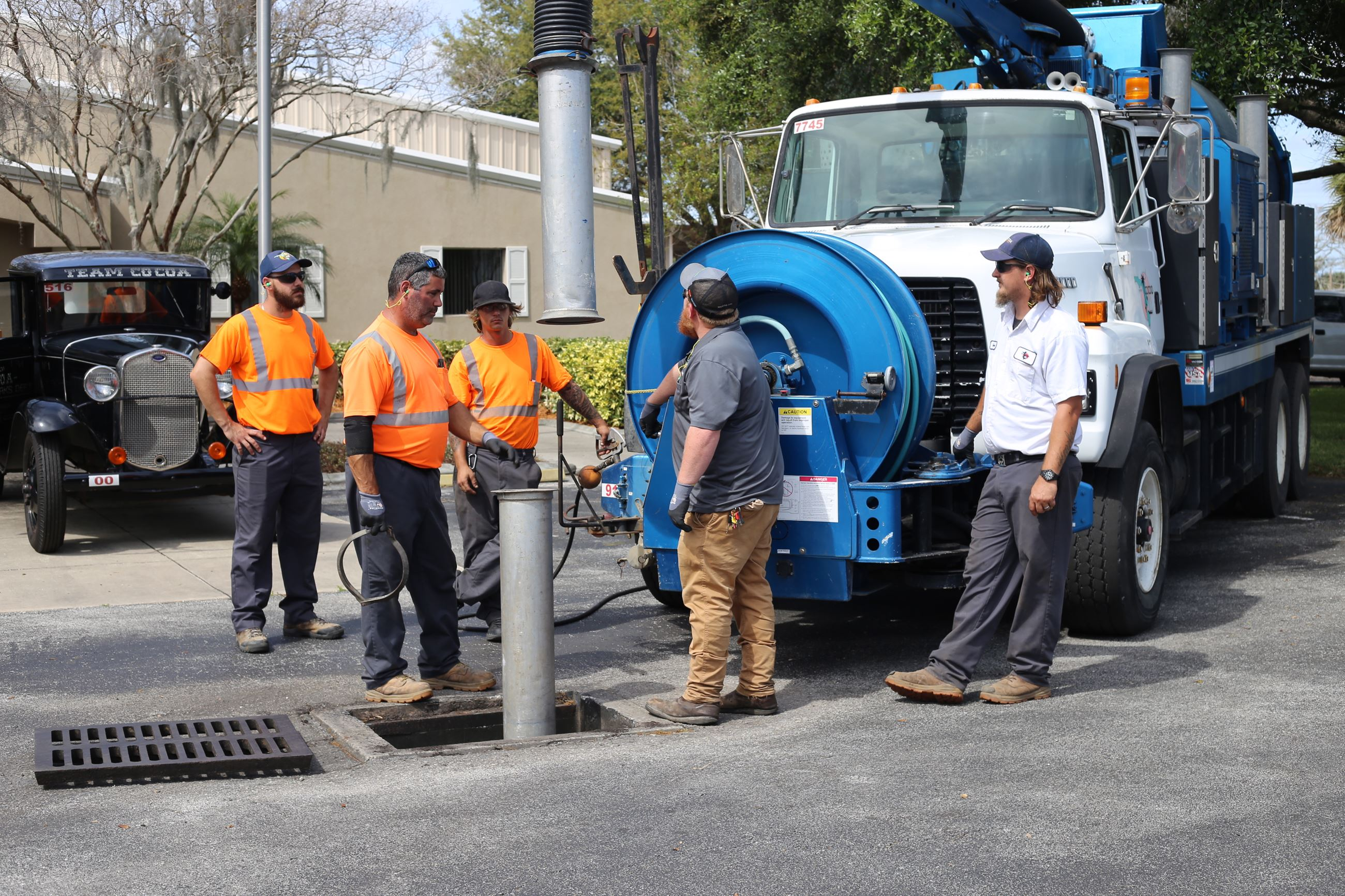 public works employees working with vacuum truck
