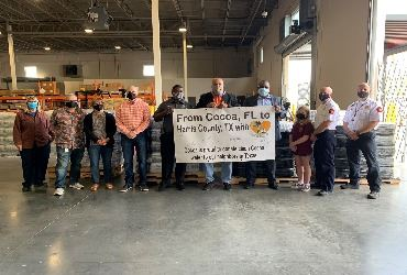 Cocoa City Council and Staff on hand in front of the pallets of water being donated to Harris County