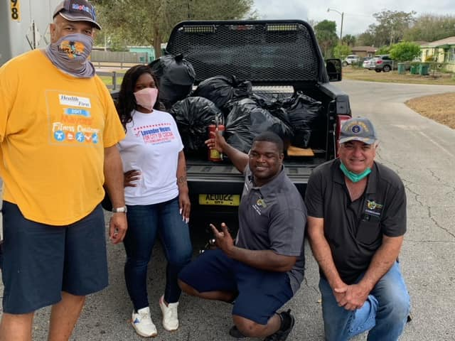 photo of Mayor Michael C. Blake and councilmembers in front of bags of trash after clean up