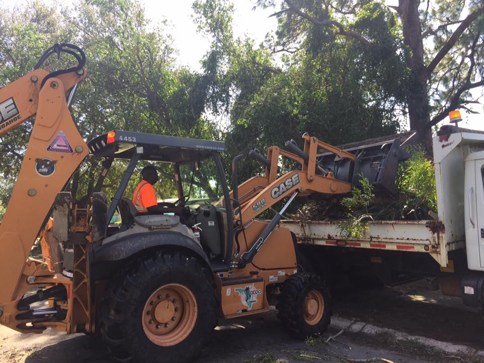Cocoa Public Works employee on a piece of equipment removing tree debris following a storm