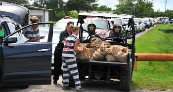 Inmates from the sherrif's work farm loading up sandbags to residents cars prior to a storm