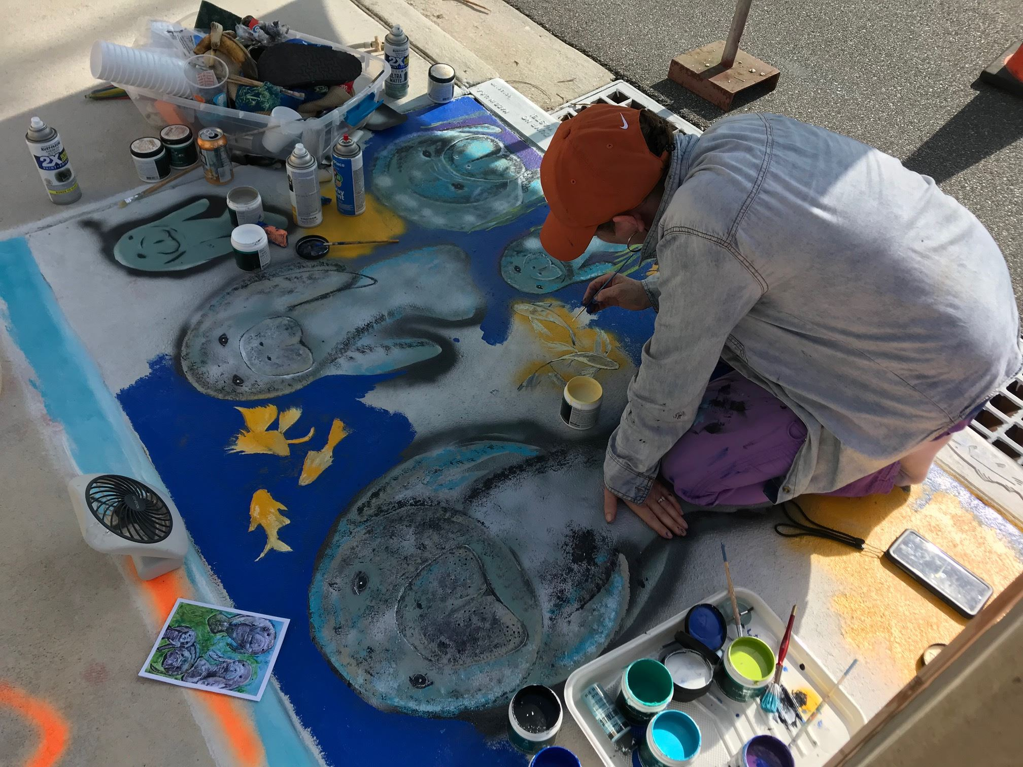 Artist Jenn Gallo painting the storm drain at Florida Avenue and Factory St. as part of the storm dr